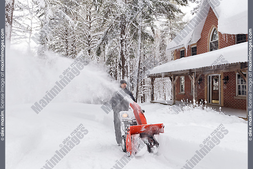 Man with a snow blower clearing a driveway in a beautiful snowy wintertime scenery of Muskoka, Ontario, Canada