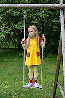 Seriously looking kid, girl on old swing. Rural, backyard.