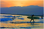 A surfer leaves the ocean at sunset along the California coast.
