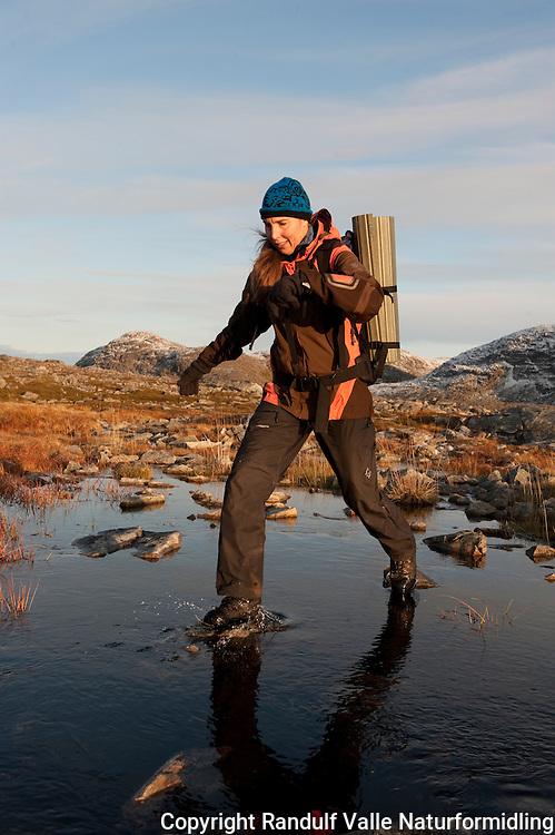 Dame går tur i høstlandskap. ---- Woman hiking in autumn landscape.