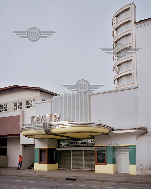 A man standing in front of the Balboa Theatre built between 1946 and 1950 by the Panama Canal Company in Gamboa, a town built in 1911, during the Panama Canal's construction, to house 'silver roll' (Afro-Antillean, non-US, non-white) workers and their dependents. No Americans were counted amongst the town's first inhabitants. By 1914, at the conclusion of Canal construction activities, Gamboa's population decreased from 700 to 173. However, when the Canal's Dredging Division was moved to the town its population revived until, in 1942, the population stood at 13,853.  <br /> <br /> The Panama Canal Zone is an area extending 8kms out, in each direction, from the waterway's central line, was a territory controlled by the United States between 1903 and 1979. After a 20 year period of joint administration, the Canal came under the full control of Panama in 1999. The Canal opened to shipping in 1914 and during its tenure was of great strategic importance to the US, enabling it to rapidly move its naval fleet between the Atlantic and Pacific Oceans. However, its economic value came not directly from shipping fees but from the stimulus to trade that the waterway created. One hundred years after it opened in 2014 it is due to have its locks upgraded to cater for the super sized container ships of the 21st Century. <br />  <br /> During the era of American administration thousands of US citizens populated the Canal Zone, living and working under US law in towns built to American standards. Not all of these people returned north after the canal came under full Panamanian control many stayed on, their identities tied to the region.