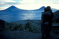 Young couple looking out over Lake Atitlan, Guatemala, at dusk