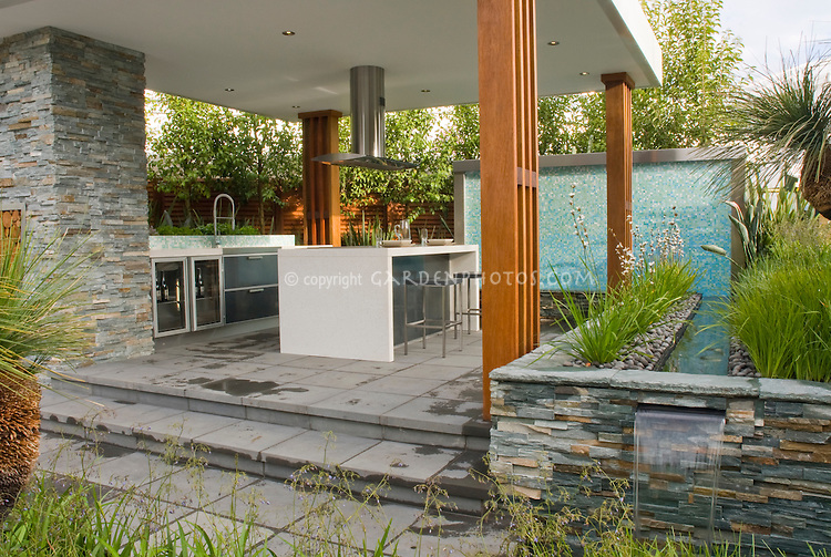 Outdoor Kitchen & Covered Patio home landscaping with dining table, waterfall water feature, ornamental grasses plants, hood, modern design, stairs steps, deck, sink, refrigerator, oven, classy and sophisticated room outside