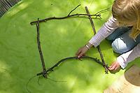 Kinder weben ein Blumenbild, Mädchen legt einen Rahmen aus Ästen