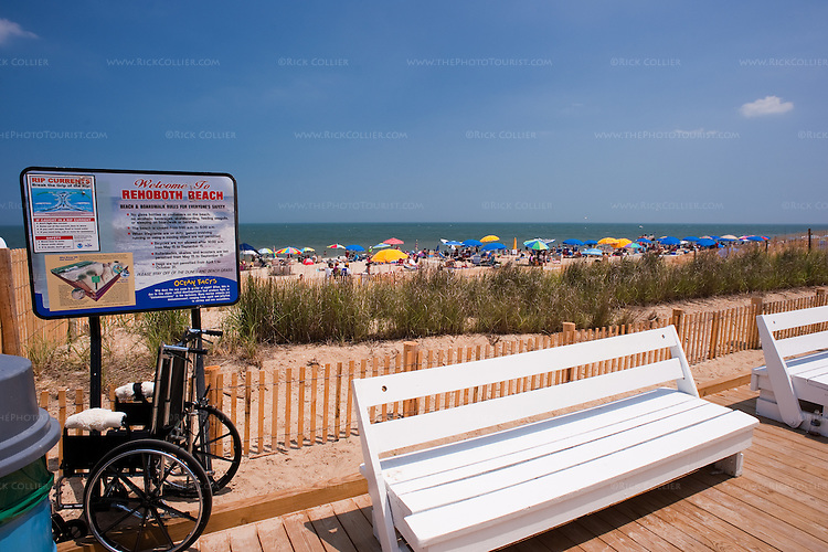 A bench and temporarily abandoned wheelchair await visitors from the packed beach beyond.  Rehoboth Beach, Delaware, USA.