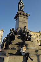 Poland, Krakow, Statue of Adam Mickiewicz, Woman with laptop computer, Rynek Glowny, Grand Square