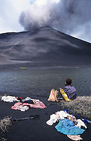 Girl washing clothes in a lake with the Mount Yasur volcano emitting smoke in the background, Tanna, Vanuatu.