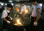 Melted glass is poured into a sushi plate mold at the Hokuyo Glass Manufacturing Company's  Blown Glass Factory in Aomori, Japan. Glass blowers at the factory churn out between 1,500 and 2,000 pieces of glass daily. (Jim Bryant Photo).....