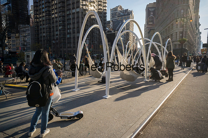 "Visitors to Flatiron Plaza in New York on Monday, November 28, 2016 interact with ""Flatiron Sky-Line"" created by architectural firm LOT. The Christmas installation is the centerpiece of the Flatiron 23rd Street Partnership's  holiday programming. The ten illuminated arches with hammocks suspended underneath engage visitors to relax and to contemplate the architectural wonders of the neighborhood, specifically the Flatiron Building. (© Richard B. Levine)"