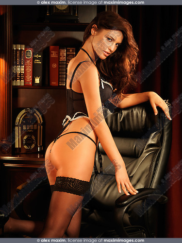Beautiful sexy young woman wearing black lingerie in an office chair