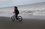 A Filipino girl rides a bicycle with her sister on the beach in Ilocos Norte, Philippines..**For more information contact Kevin German at kevin@kevingerman.com