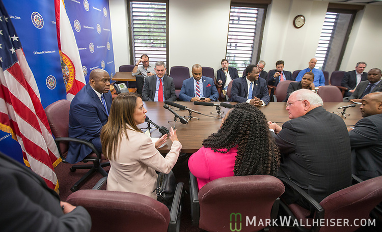 """Earvin """"Magic"""" Johnson, retired professional basketball player and current president of operations for the Los Angeles Lakers of the NBA, left, listens as Lourdes Rivas, CEO of Simply Healthcare speaks during a meeting with the Florida Senate Democratic Caucus  about health care at the Florida Capitol in Tallahassee Florida March 13, 2017."""