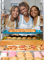 Portrait of small business owners of Big Mamma's bakery.  The three sisters are surrounded by rolls, bread and donuts.  For over 60 years the recipes of Big Momma's have been passed down through the generations. These recipes use only natural ingredients, no artificial preservatives coloring, or flavoring.