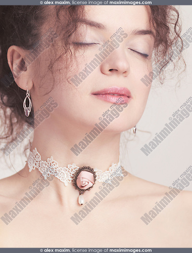 Closeup of young beautiful woman face wearing a pink rose lace choker on her neck