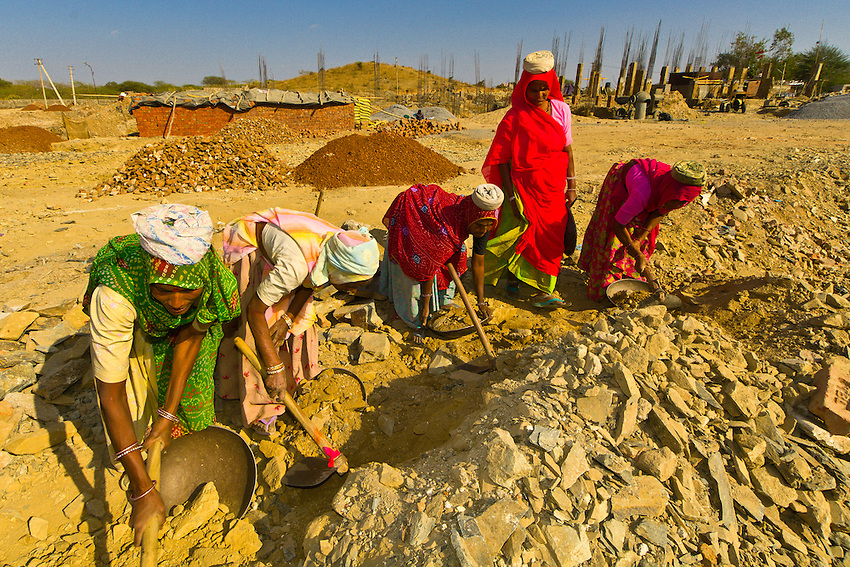 Woman breaking up and carrying rocks at a construction site, Udaipur, Rajasthan, India