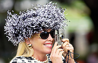 Race-goer wearing a typical Ascot fashion hat while photographing the day's events on a small camera at Royal Ascot Races