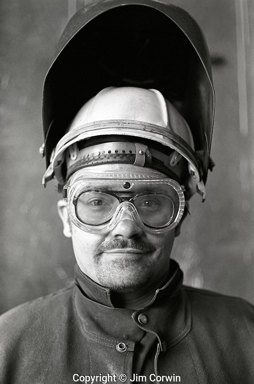 Welder standing with goggles and metal welding face guard