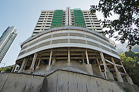 Magazine Court, a 13-story apartment building in Magazine Gap Road, Hong Kong, undergoing some refurbishment and covered in traditional bamboo scaffolding. Located on a bend in the road and overlooking Central, the front half of the property is perched on concrete stilts, giving it a somewhat precarious look