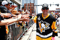 Pascal Dupuis #9 of the Pittsburgh Penguins greets fans during the Stanley Cup victory parade in downtown Pittsburgh, Pennsylvania on June 15, 2016. (Photo by Jared Wickerham / DKPS)