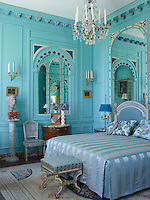 Bright colours in unexpected art shades are a feature of this restored manor house as exemplified by this panelled bedroom painted a striking turquoise