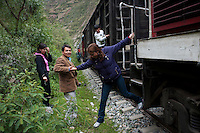 Passengers get off the train during a stop caused by a landslide.