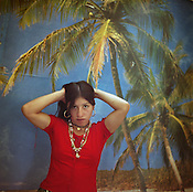 A Roma girl stands pretending to be a Western supermodel, in front of a photo-mural of a beach scene, in a new house in the Roma camp of Sintesti. Photo-posters of beach scenes, or forest scenes, are now popular within the camp, as is the desire to imitate Western women and styles..