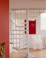 A spiral staircase takes up less space than a traditional one but can nevertheless dominate a room