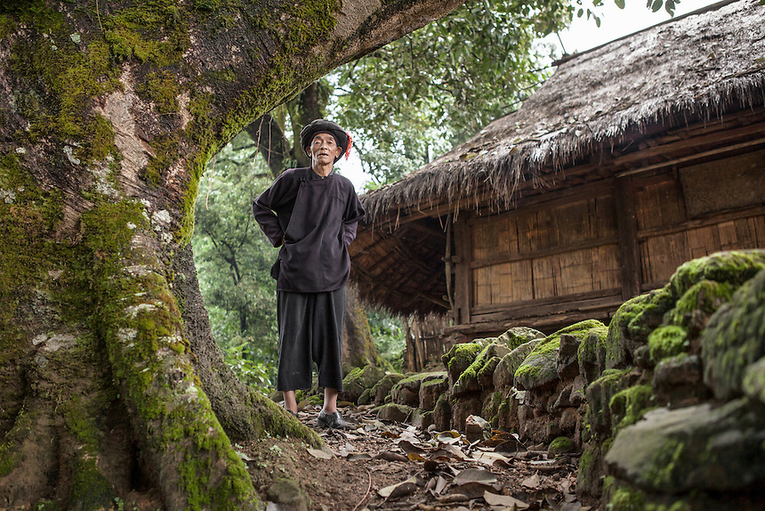"""A Wa elder stands in front of his traditional house in the village of Wengding. The Wa, which literally means """"mountain dwellers"""", is the hilltribe that inhabit the Sino-Burmese. Known as one of the last headhunting tribe until mid-twentieth century, their population in both countries now approximately no more than one million. In the homogenous society of modern China, Wa is one of more than 50 officially state-recognized ethnic minorities. They can be found around the southwestern corners of Yunnan province."""