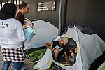A family from Afghanistan has lunch inside their tent while speaking to a couple who had twins as they traveled through Turkey, at a makeshift camp in the Budapest Keleti railway station. The family wants to settle in Sweden.<br /> <br /> Hundreds of refugees from mostly Syria and Afghanistan gather at the Budapest Keleti railway station waiting for trains to leave for destinations such as Austria, Germany and Sweden, in Budapest, Hungary, on Tuesday, Sept. 8, 2015. Hungary's Prime Minister Viktor Orban created an anti-refugee campaign to generate hate against those fleeing war in their home countries. The country is currently 50% xenophobic and the government has become increasingly authoritarian.