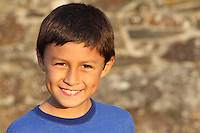 Portrait of a young smiling boy near sunset by an old wall