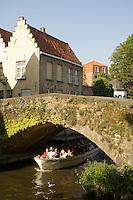 Belgium, Bruges, Tourist sightseeing boat on canal passing under bridge