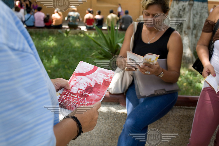 """Lawyer Sol Marina Lamon distributes leaflets and talks with women about security and protection measures and the new """"Organic Law for the right of women to a life free of violence"""" in the La Vega neighbourhood of Caracas."""