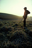 farmer leans on pitchfork early morning sunrise frosty fields