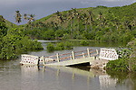 A broken and flooded bridge at Tangun Aan on Lombok, Indonesia. In the background the hills and palm trees of Indonesia.