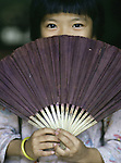 A curious girl hides from behind a hand fan in Hanoi, North Vietnam.  (Jim Bryant Photo).....