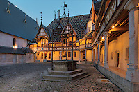 Well in the courtyard of Les Hospices de Beaune, or Hotel-Dieu de Beaune, a charitable almshouse and hospital for the poor, built 1443-57 by Flemish architect Jacques Wiscrer, and founded by Nicolas Rolin, chancellor of Burgundy, and his wife Guigone de Salins, in Beaune, Cote d'Or, Burgundy, France. The buildings, set around an internal courtyard, are in Northern Renaissance and Flamboyant Gothic style, with half-timber galleries, ornate rooftops with Burgundian glazed tiles in geometric patterns and dormer windows. The hospital was run by the nuns of the order of Les Soeurs Hospitalieres de Beaune, and remained a hospital until the 1970s. The building now houses the Musee de l'Histoire de la Medecine, or Museum of the History of Medicine, and is listed as a historic monument. Picture by Manuel Cohen