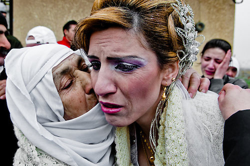 The mother  of the bride,  Sadiqa Maraa'I,  is giving a last kiss to her daughter. They might never see each other again: the mother is denied the entry in Israel, and the daughter can not come back in Syria.