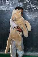 Laddu, 3, poses for a portrait with a soft toy in the Guria Non-Formal Education center in the middle of the Shivdaspur red light district, Varanasi, Uttar Pradesh, India on 20 November 2013. Guria uses the soft toys as a form of therapy for the children of the women in prostitution and also use it as signals of the children's emotional wellbeing.