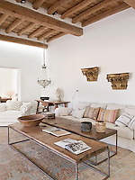 A beaded glass chandelier hangs over a trestle table in one corner of the living room furnished with a pair of large rustic wood and metal coffee tables and a comfortable sofa and armchair