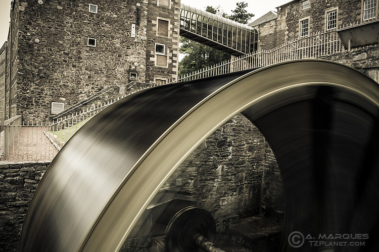 Spinning Waterwheel at the site of Mill Number Four, New Lanark, Scotland. <br /> For years, the machinery in the cotton mills was powered by waterwheels, before being replaced by water turbines. <br /> The New Lanark Mills operated until 1968. <br /> Nowadays, with a population of around 200 and many of the old mill buildings converted to homes, New Lanark is listed as a UNESCO World Heritage site.