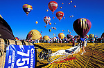 Envelope being rolled out with hot air balloons rising in the background at the International Balloon Fiesta, Albuquerque, New Mexico USA