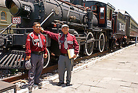Two railway workers beside a steam  locomotive  at the Museo Nacional de los Ferrocarriles Mexicanos or National Railway Museum in the city of Puebla, Mexico
