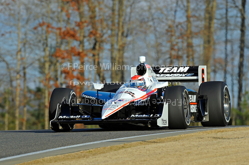 Ryan Briscoe (#6) crests the hill at past turn 12.