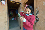 Kabita Chepang, 10, combs her hair as she prepares for school in the morning at her home in the village of Tanglichowk in the Gorkha District of Nepal. In the aftermath of the April 2015 earthquake that ravaged Nepal, the ACT Alliance helped people in this village with a variety of services, including latrines, emergency shelter, livelihood projects and school construction.  <br /> <br /> Parental consent obtained.