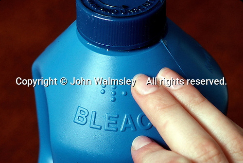 Reading the braille label on a bottle of bleach.