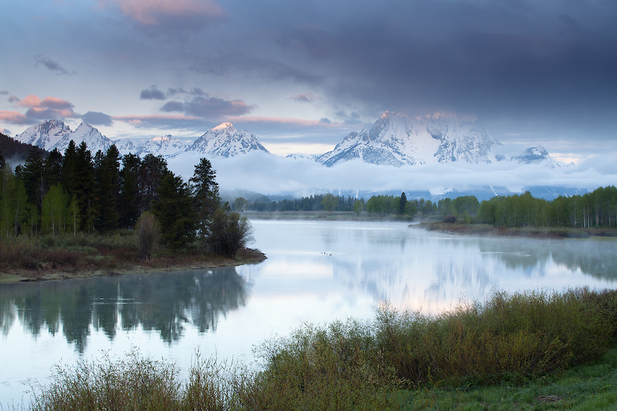 The cool morning light highlights the peaks of the Tetons.