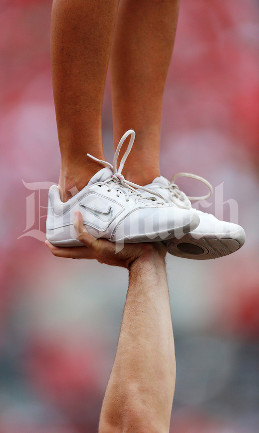 A male alumni cheerleader holds up a female alumni cheerleader during of a football game between The Ohio State University Buckeyes and the Kent State University Golden Flashes on Saturday, September 13, 2014 at Ohio Stadium in Columbus, Ohio. (Columbus Dispatch photo by Fred Squillante)