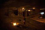 A young boy keeps warm by a fire in the Noveno Barrio, one of the oldest maquila worker settlements in the city.