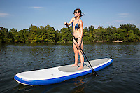 Young Attractive Woman on Stand Up Paddle Board, SUP, in the Blue Waters of Lady Bird Town Lake Austin, Active Life Fitness Concept. Austin, Texas.