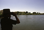 A U.S. Border Patrol agent in Del Rio, Texas, searches the Rio Grande River for illegal aliens.  While the traditional mission of the United States Border Patrol has always been the detection and prevention of the illegal entry of aliens and smuggling of illegal contraband into the United States anywhere other than a designated port-of-entry, the dawn of the age of terrorism within our nation has added a new and high priority mission: to detect and prevent the entry of terrorists and their weapons into the United States. Jim Bryant Photo..&copy;2006. All Rights Reserved.